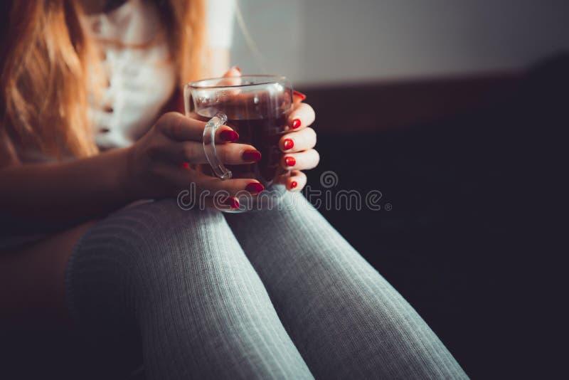 Мягкое фото женщины на чае или кофе кровати выпивая Женщина в kneesocks на темной предпосылке с чашкой стоковое фото rf