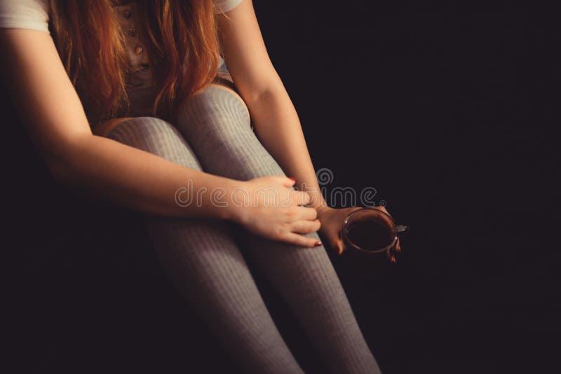 Мягкое фото женщины на чае или кофе кровати выпивая Женщина в kneesocks на темной предпосылке с чашкой стоковое изображение rf
