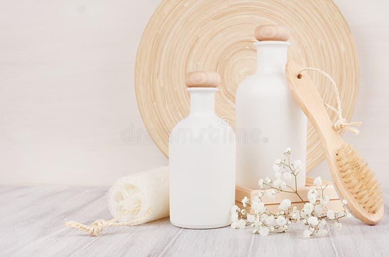 Мягкое элегантное оформление ванной комнаты, шаблон белых бутылок с гребнем, цветков косметик на белой деревянной доске, космосе  стоковое изображение