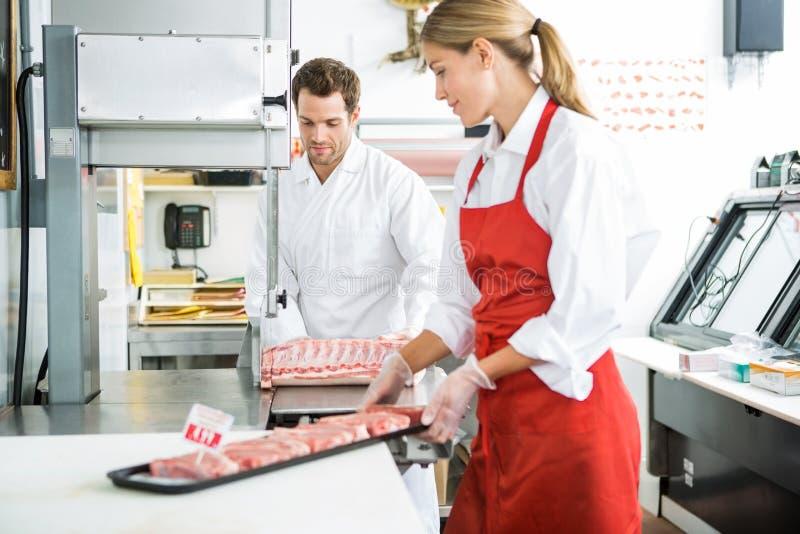 Мясники обрабатывая мясо в магазине стоковая фотография rf