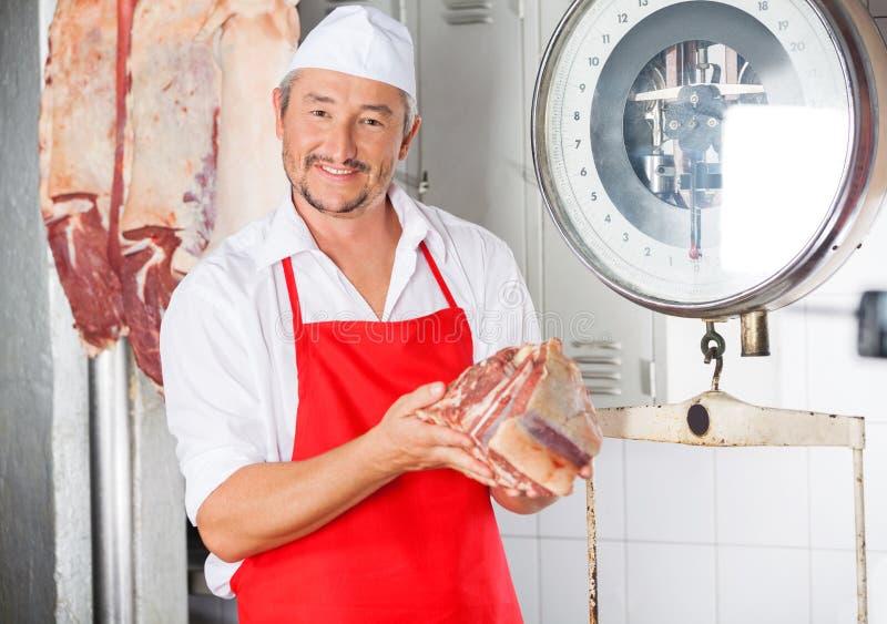 Мясник держа мясо в палачестве стоковые фотографии rf