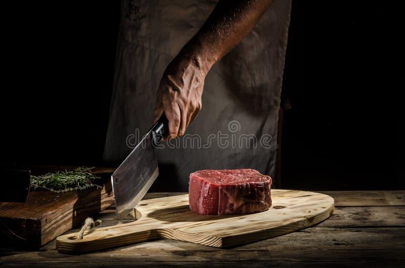 Мясник шеф-повара подготавливает стейк говядины стоковое фото rf