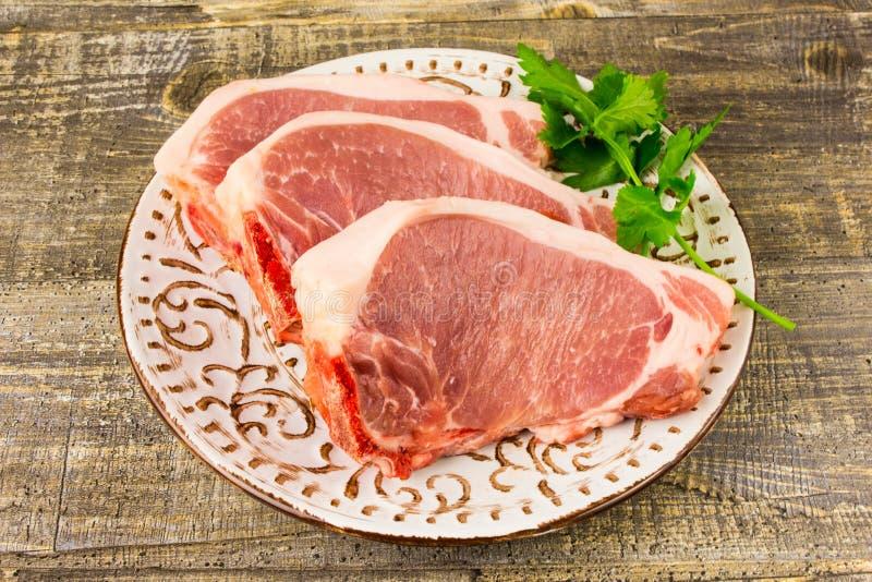 Мясо белой плиты сырцовое отрезанное на деревянном столе, взгляд сверху Еда, нож, ветви зеленых цветов стоковое изображение