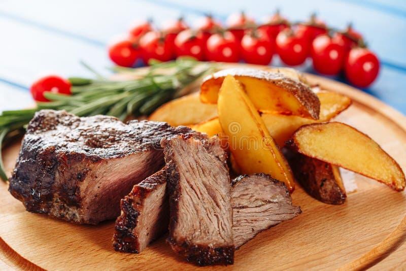 Мясо говядины стейка зажарило сваренную отрезанную сторону картошки стоковые фото