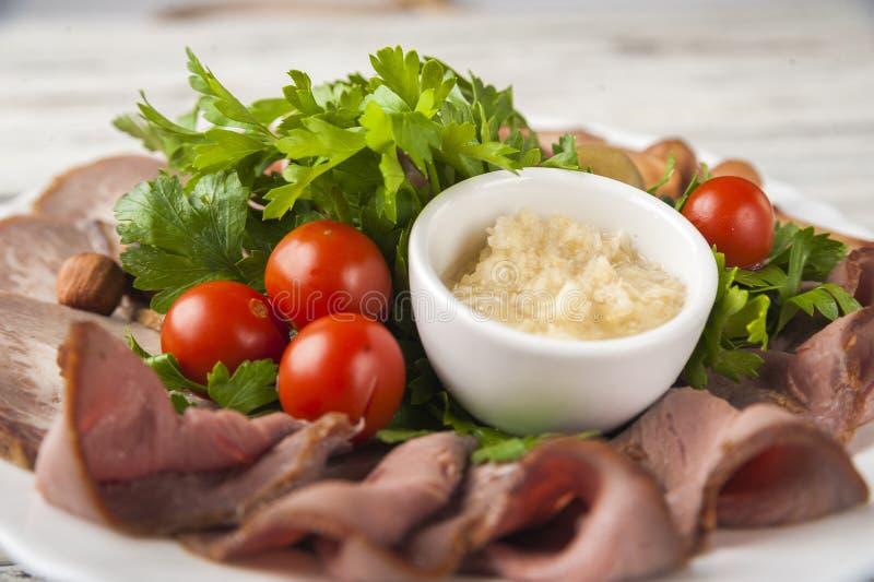 Мясо и сосиска отрезали на плите с гайками, соусе чеснока Пастрома, испеченная ветчина, chorizo, бекон, оливки, томаты вишни на a стоковые изображения rf