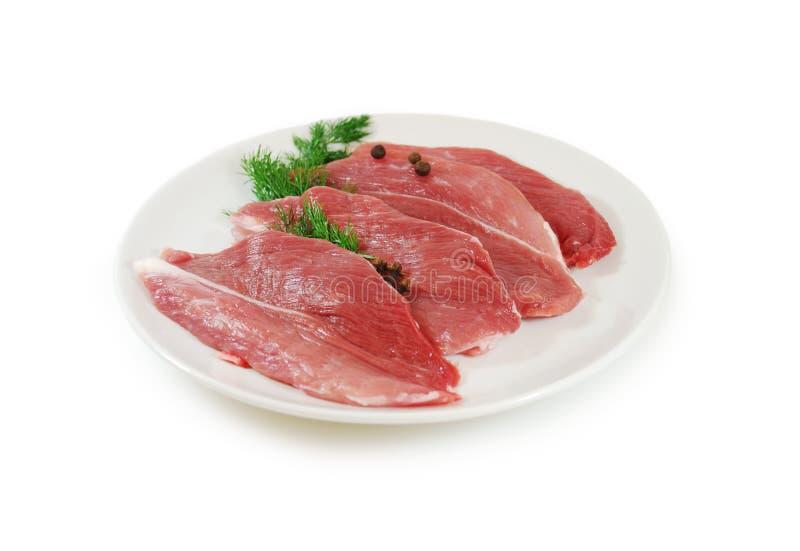 мясо сырцовое Стейки свинины с укропом на блюде изолированном против белой предпосылки стоковое фото rf
