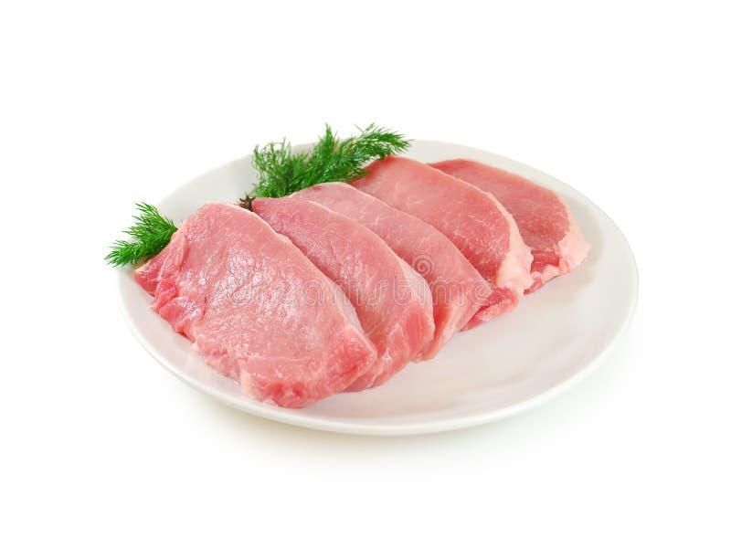 мясо сырцовое Стейки свинины с укропом на блюде изолированном против белой предпосылки стоковые фото