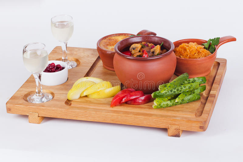 Мясо с грибами в баке, cocotte julienne, соленьях, яблоках, доске водочки деревянной изолировало белую предпосылку стоковые фотографии rf