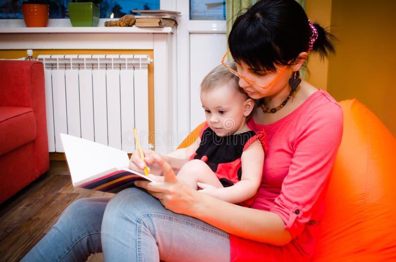 Младенец в костюме ladybird рисует с ее матерью стоковое изображение