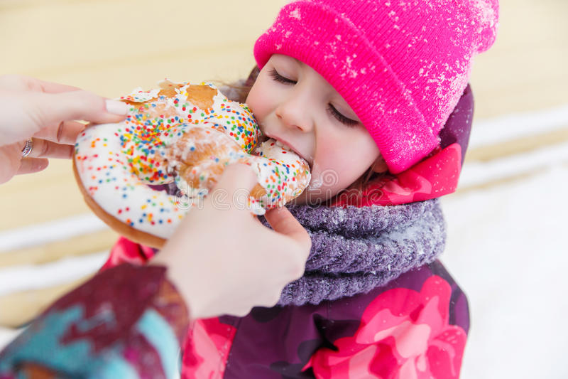 Младенец ест бейгл в парке стоковые изображения