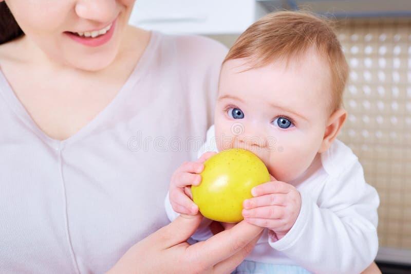 Младенец ест желтое яблоко Ребенок стоковые изображения rf