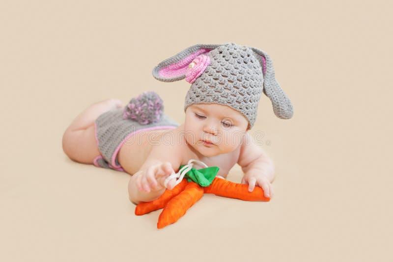 Младенец зайчика пасхи играя с морковью стоковое фото rf
