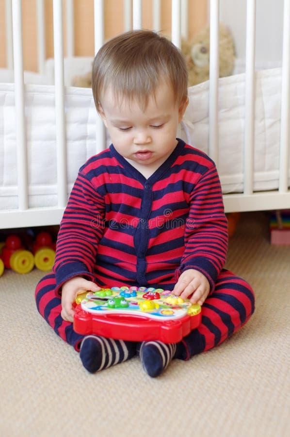 Младенец играет музыкальную игрушку стоковое фото rf