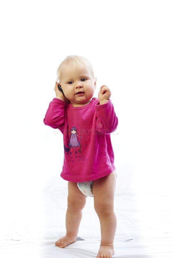 Младенец играет с телефоном над белой предпосылкой стоковые фото
