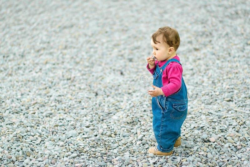 Младенец играя на пляже и кладет камешек в рот стоковая фотография rf