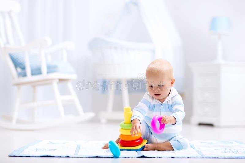 Младенец играя с пирамидой игрушки Игра детей стоковое фото