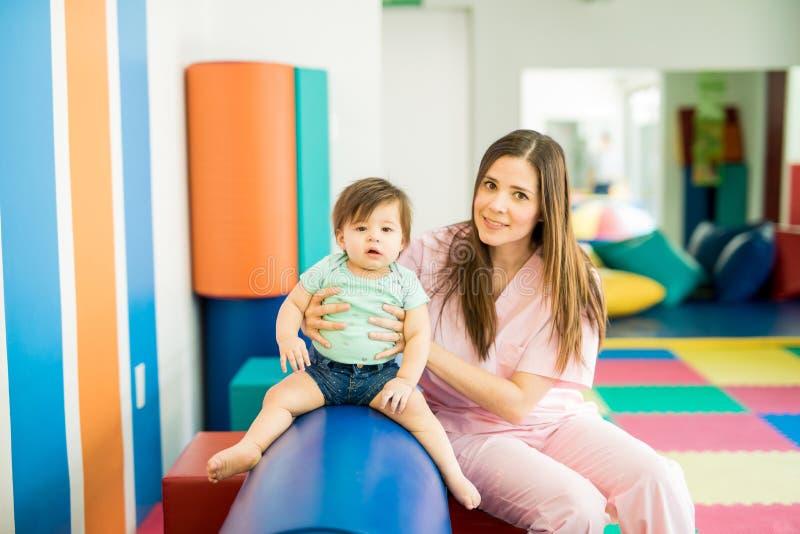 Младенец и терапевт в школе стоковые фото