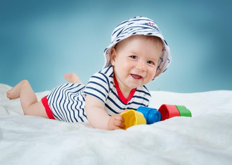 Младенец 9 месяцев старый лежа в кровати на белом одеяле стоковое изображение