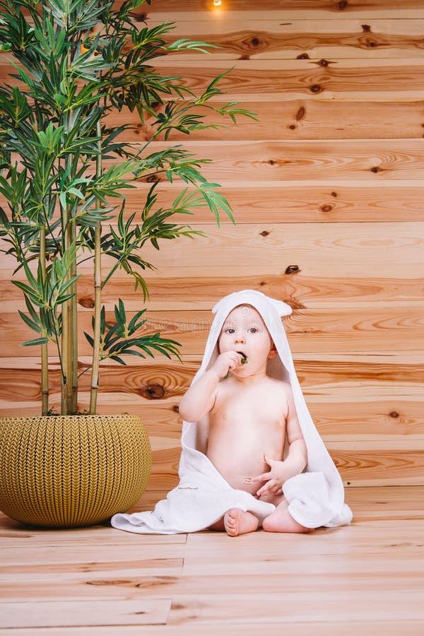 Младенец обернутый в белом полотенце сидя на деревянной предпосылке около бамбукового дерева в баке стоковые фотографии rf