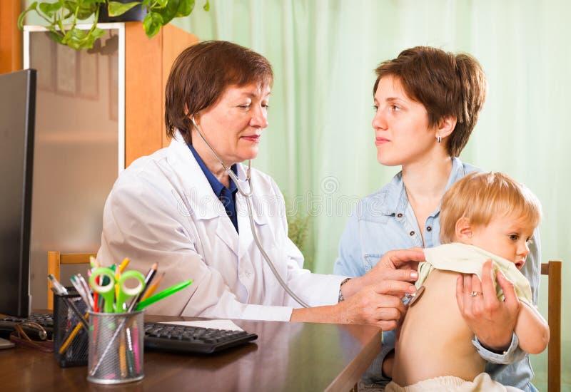 Младенец доктора examing с стетоскопом стоковые изображения
