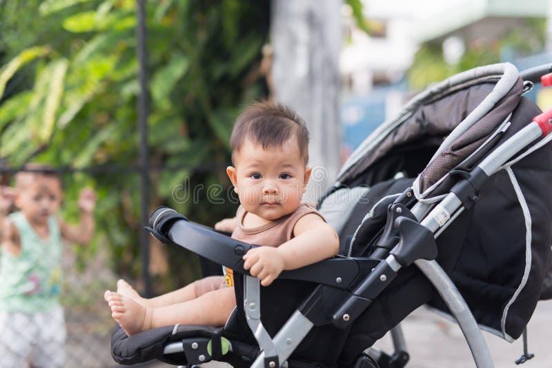 Младенец сидит на экипаже самостоятельно стоковая фотография rf
