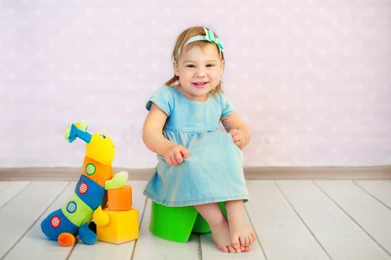 Младенец сидя на горшочке в домашнем интерьере стоковое фото rf