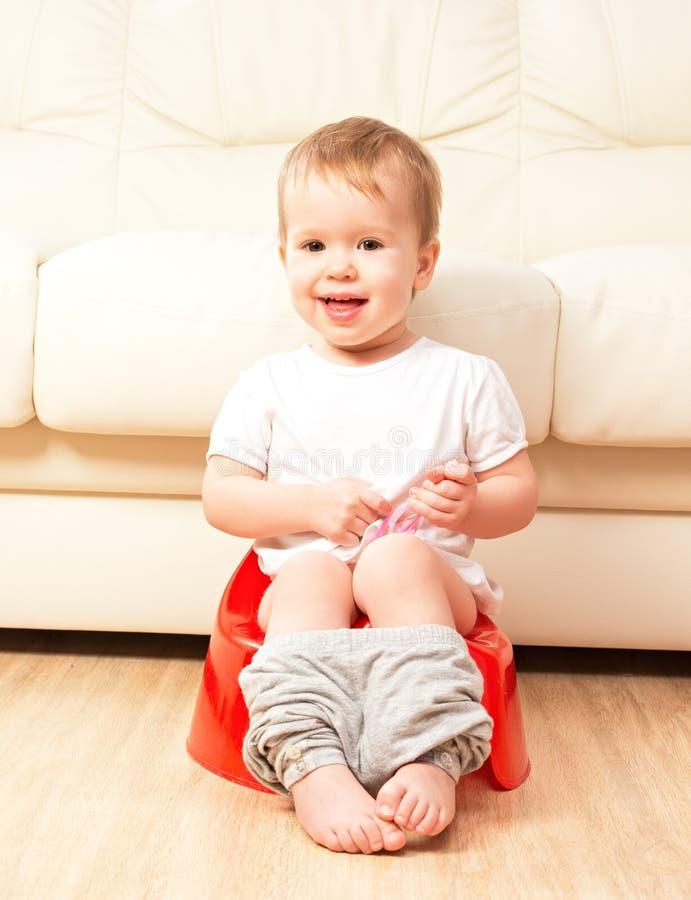 Младенец сидя на горшочке в туалете стоковое фото