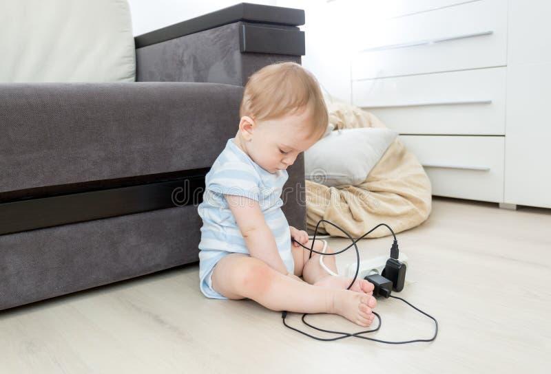 Младенец сидя самостоятельно в живущей комнате и играя с электрическим ca стоковое фото rf
