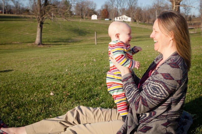 Младенец смеясь над с мамой снаружи стоковая фотография rf