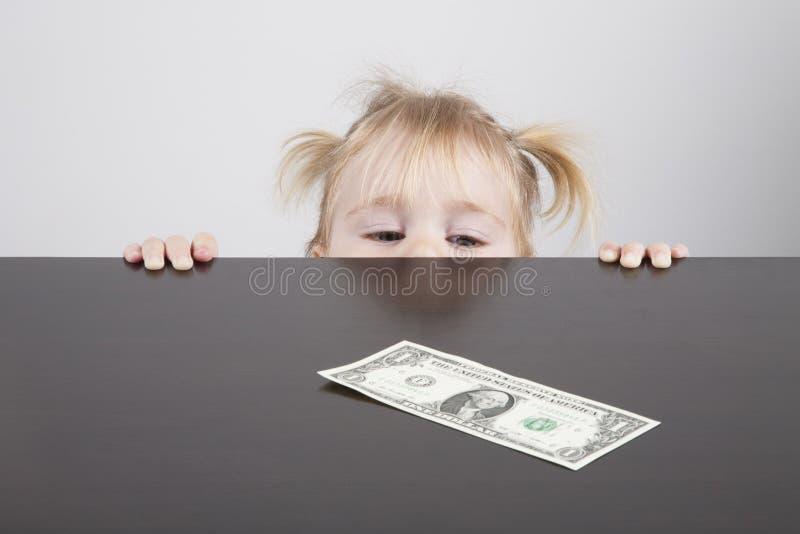 Младенец смотря банкноту доллара горизонтальную стоковые фотографии rf