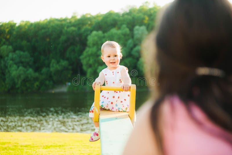 Младенец счастливо играя с родителями снаружи на солнечном горячем источнике или стоковая фотография rf