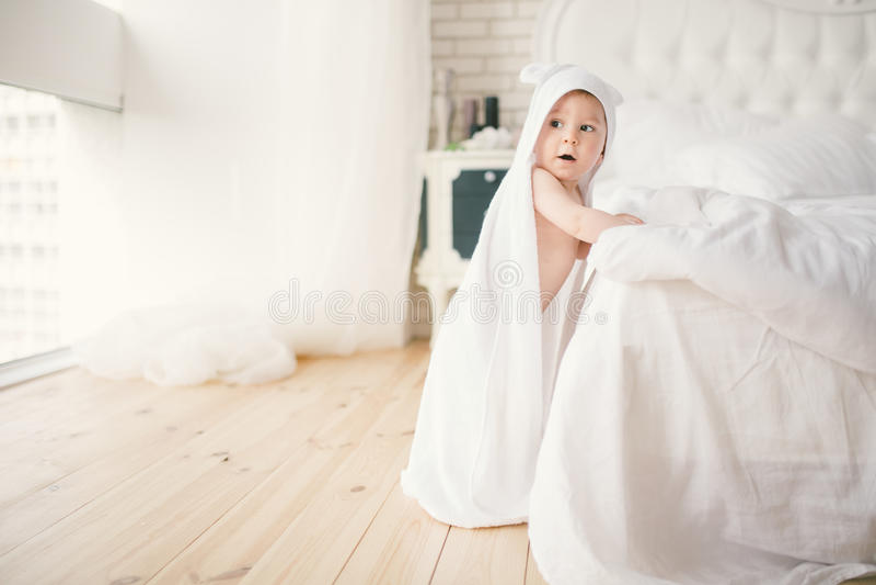 Младенец Newborn младенца пятимесячный старый в спальне рядом с большой белой кроватью на деревянном поле обернутом в белом бамбу стоковые изображения rf