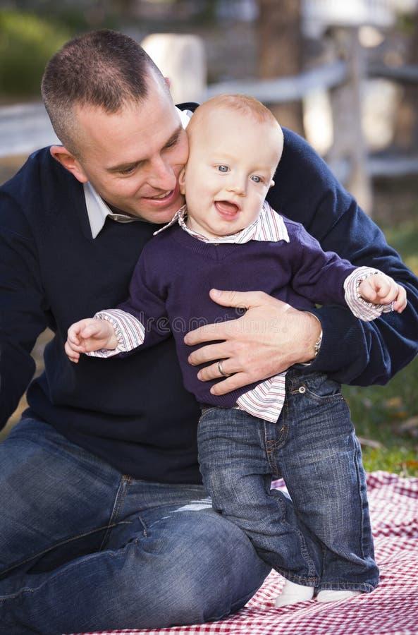 Младенческий мальчик и молодая воинская игра отца в парке стоковая фотография rf