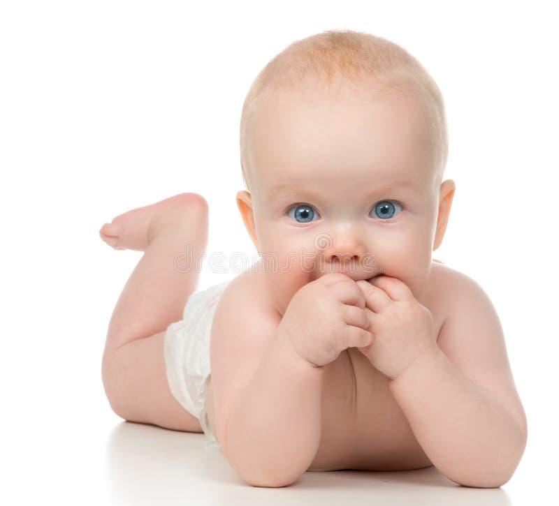 Младенческий ребёнок ребенка лежа с руками в рте стоковая фотография