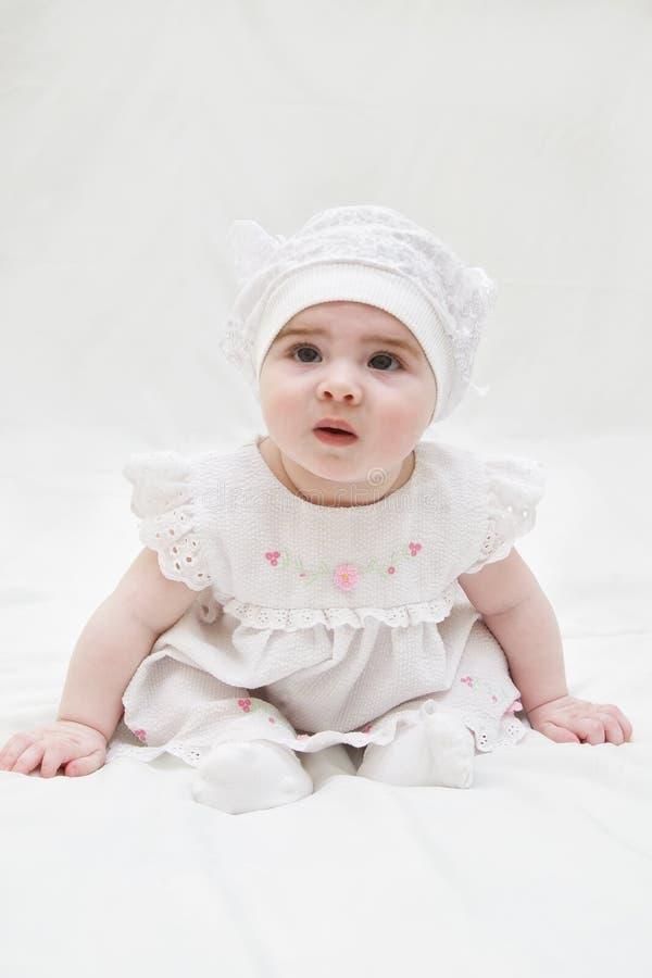 Младенческое время девушки 10 месяцев на белой предпосылке стоковое фото