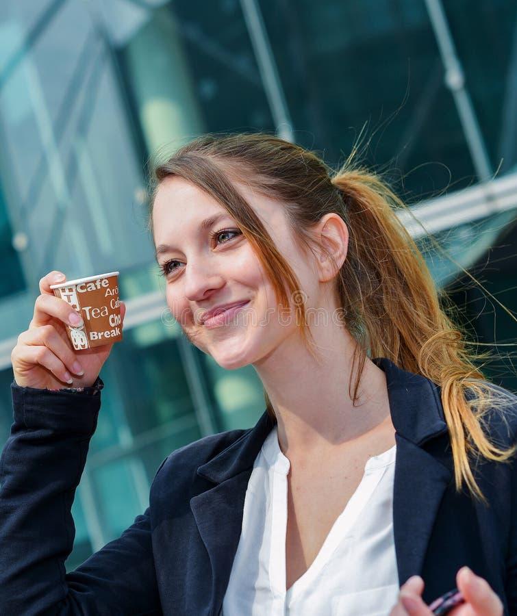 Младший администратор имея перерыв на чашку кофе перед ее компанией стоковая фотография