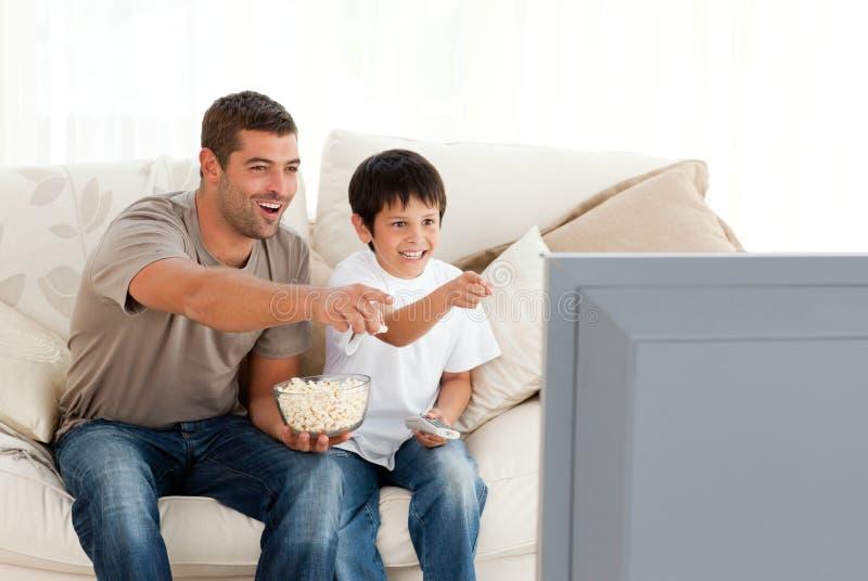 наблюдать телевидения сынка отца счастливый стоковая фотография