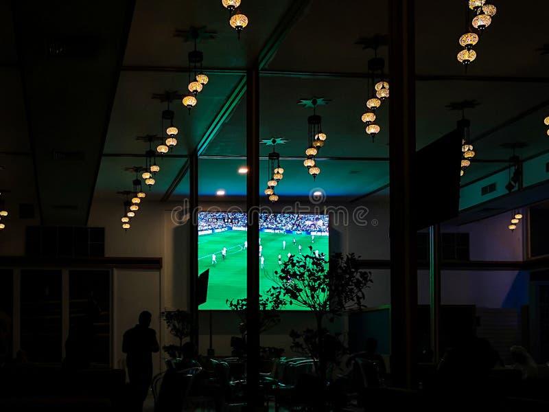 Наблюдающ футбольный матч на экране внутри кафа/ресторана вечером стоковое фото