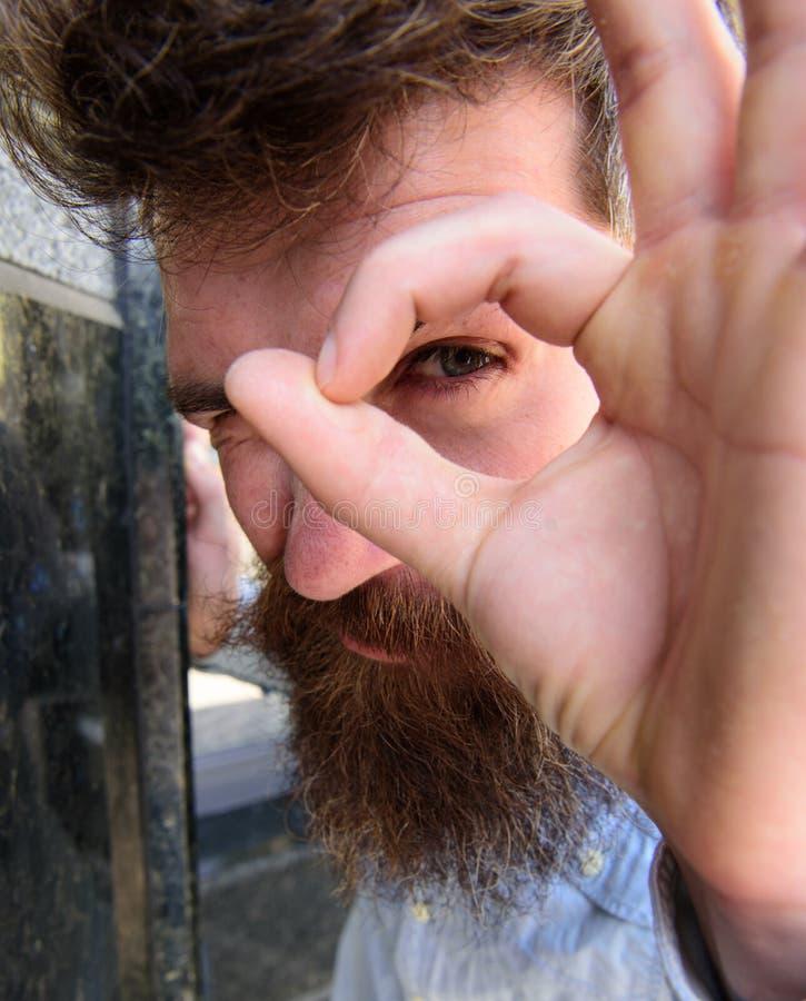 Наблюдая концепция Гай смотрит подозрительным через одобренный жест, конец вверх Битник при tousled волосы смотря, наблюдающ стоковое изображение