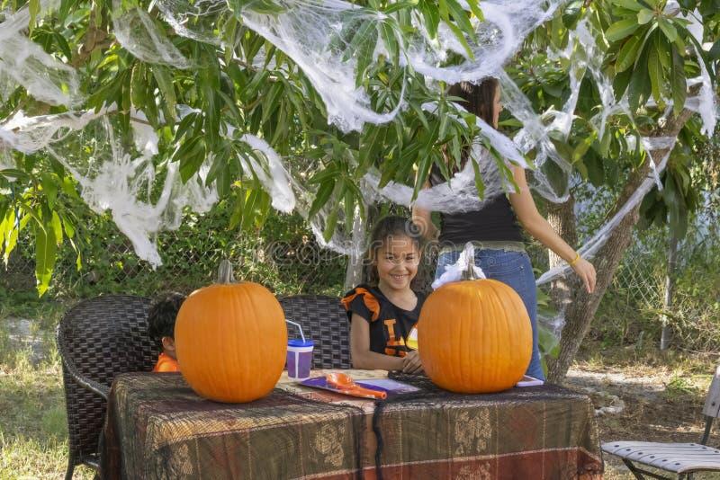 Наборы молодые девушки смешанн-гонки рядом с ее братом на таблице настроенной для высекать тыквы стоковое изображение