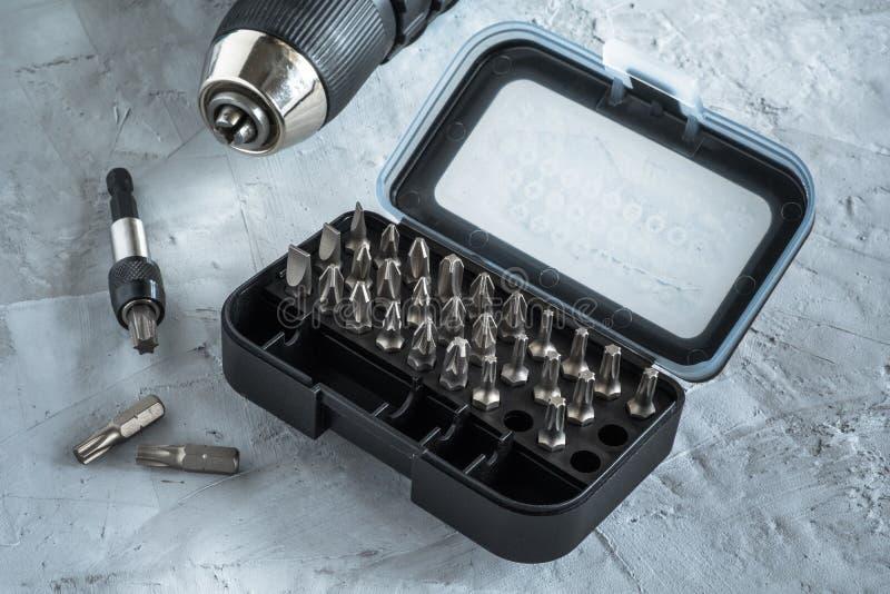 Набор битов для отвертки в черном случае Инструмент строительства Серый фон стоковое фото