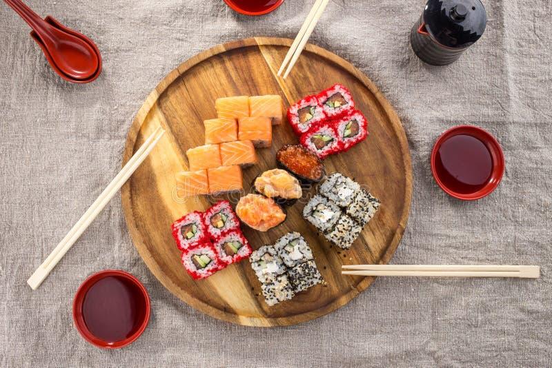 Набор крена maki суш ресторана японской кухни на деревянной круглой доске с палочками на предпосылке ткани серой стоковое изображение rf