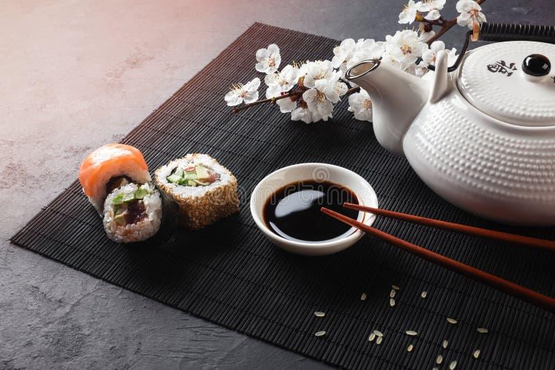 Набор кренов суш и maki с ветвью белых цветков и чайника с чаем надписи зеленым на каменной таблице стоковые изображения rf