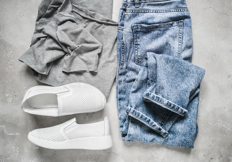 Набор одежды женщин обмундирования - белые кожаные тапки, футболка и голубые джинсы на серой предпосылке, взгляде сверху o стоковая фотография rf