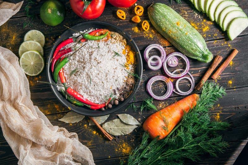 Набор продуктов для подготовки индийского pilaf от риса и овощей со специями, взглядом сверху стоковые изображения rf