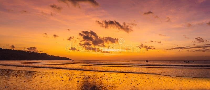 Набор солнца Бали пляжа Jimbaran около международного аэропорта Ngurah Rai, расположенного на рыбном базаре Pantai Kedonganan Jim стоковая фотография