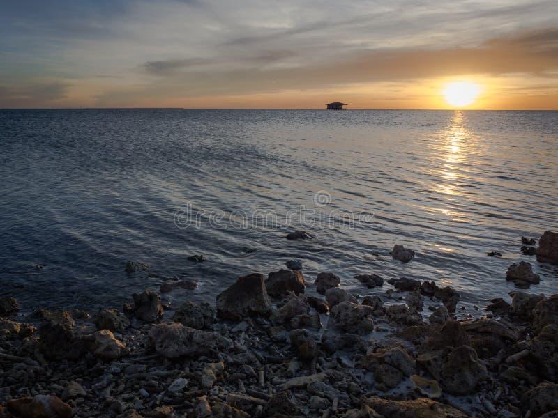 Набор солнца за скалистым пляжем с красивым оранжевым небом и голубой морской водой стоковое изображение