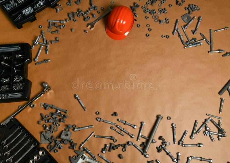 Набор стальных конструкционных инструментов на заднем плане с оранжевым шлемом стоковые фото