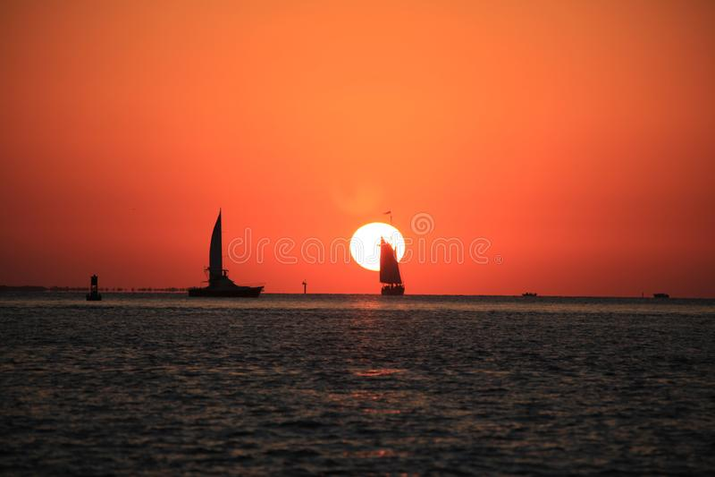 Набор, шлюпка и плавание Солнца стоковые изображения