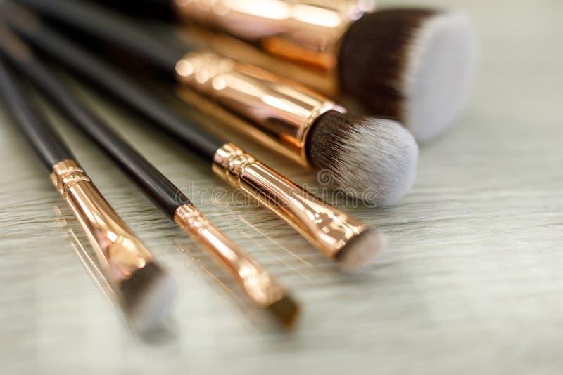 Набор щеток для макияжа лежит на таблице в салоне красоты стоковые изображения rf